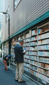 Hombre observando libros en un estante